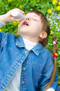 Allergy little girl spraying her nose outdoors Stock Photos