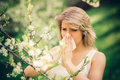 Allergy woman with pollen in springtime near tree in bloom Royalty Free Stock Photos