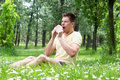 Allergy young male blowing his nose outdoors having problem with Stock Image