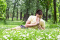 Allergy young male blowing his nose outdoors sneezing among flowers having problem with Stock Images