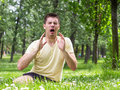 Allergy young male sneezing outdoors having problem with Royalty Free Stock Photo