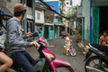 Alley in ho chi minh city view of an district phu nhuan during daytime a little boy stands by his tiny white bicycle closer to Royalty Free Stock Photos