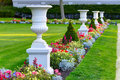 Alley with white flowerpots in the beautiful flowerbed Royalty Free Stock Photo