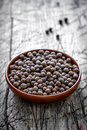 Allspice peppercorns in a bowl on a vintage wooden table Royalty Free Stock Image