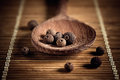 Allspice in a wooden spoon on the table Royalty Free Stock Photo