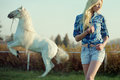 Alluring blonde beauty with majestic horse in the background Royalty Free Stock Photos