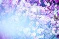 Alluring blonde woman in blooming flowers