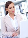 Allvarlig nätt affärskvinna using laptop Arkivfoton