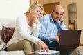 Allvarligt mogna par med bärbara datorn Arkivbild