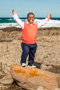 The almighty dwarfish african man throwing his hands up laughing openly with a rocky beach in background Stock Photography