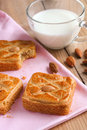 Almond biscuits closeup on pink tablecloth with a cup of milk on wooden rustic table Stock Image
