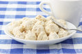 Almond cookies and cup in white plate white on checkered tablecloth Royalty Free Stock Images