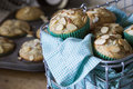 Almond poppyseed muffin in blue wrapping with muffin tin metal wire basket of breakfast muffins slivered almonds green paper Stock Photos