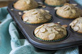 Almond poppyseed muffin in blue wrapping with muffin tin silver of breakfast muffins slivered almonds green paper cups gingham Stock Photo