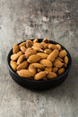 Almonds in black bowl on wood Royalty Free Stock Photo