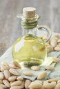 Almonds oil and peeled nuts on wooden table Royalty Free Stock Photos