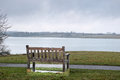 Alone a lone empty bench beside a path along the water s edge of a lake in drab weather Royalty Free Stock Photo