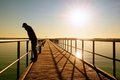 Alone man on pier and look over handrail into water. Sunny clear sky, smooth water Royalty Free Stock Photo