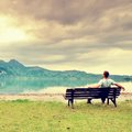 Alone  man sits on bench beside an azure mountain lake. Man relax Royalty Free Stock Photo