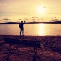 Alone traveler with backpack. Man  on sea beach at wooden bench, cold sunny autumn evening Royalty Free Stock Photo