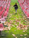 Alone woman in auditorium walks among seats empty Royalty Free Stock Photography