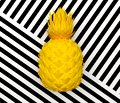 Alone yellow abstract pineapple isolated on a background with a black and white stripe. Tropical exotic fruit. 3D rendering.