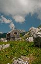 Alpine cottage in the mountains Stock Images