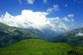 Alpine meadows, lake, mountains and lots of white clouds with beautiful summer landscape Royalty Free Stock Photo