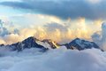 Alpine mountain landscape with peaks covered by snow and clouds Royalty Free Stock Photo