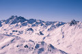 Alpine panorama showing snow covered mountains clear blue sky Stock Images