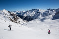 Alpine panorama showing snow covered mountains clear blue sky skiers preparing route Stock Photos