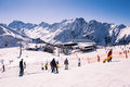 Alpine panorama showing snow covered mountains clear blue sky skiers snowboarders piste Stock Images
