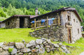 Alpine stone shepherd s hut in a peasant village in the background of the alps northern italy Stock Photos
