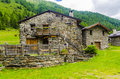 Alpine stone shepherd s hut in a peasant village in the background of the alps northern italy Royalty Free Stock Images