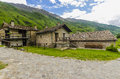 Alpine stone shepherd s hut in a peasant village in the background of the alps northern italy Royalty Free Stock Image