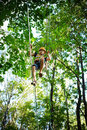 Alpinism boy walking on the rope high in the park with insurance Stock Photos