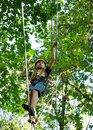 Alpinism boy walking on the rope high in the park with insurance Stock Photo