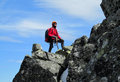 Alpinist alpine climber walking to the top of the mountain through the snow and stones a man – on rocks summit people with big Royalty Free Stock Images