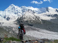 Alpinist tourist with big backpack in Caucasian mountains, near Tetnuldi Royalty Free Stock Photo
