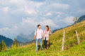 Alps couple hiking in bavarian mountains of men and women on mountain summit or alpine grassland the enjoys the panorama the Royalty Free Stock Photos