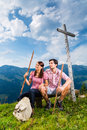 Alps hiking couple takes break in mountains young sitting on mountain summit at cross the bavarian and enjoys the panorama the Royalty Free Stock Images