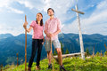 Alps hiking couple takes break in mountains young standing on mountain summit at cross the bavarian and enjoys the panorama the Royalty Free Stock Images