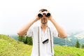 Alps man on mountains with field glasses hiking young in the bavarian looking through a or binocular enjoying the panorama in the Royalty Free Stock Image