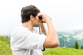 Alps man on mountains with field glasses hiking young in the bavarian looking through a or binocular enjoying the panorama in the Royalty Free Stock Photography