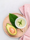 Alternative health care fresh avocado , leaves and oil on marbl Royalty Free Stock Photo