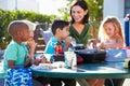 Alunos e professor elementares eating lunch Imagem de Stock