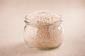 Amaranth expanded grains roasted in glass jar on material Royalty Free Stock Photos