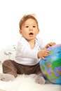 Amazed baby with world globe sitting on fur blanket Stock Image