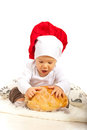 Amazed chef baby with bread looking at and sitting on floor Stock Photos