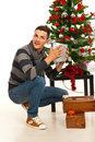 Amazed christmas man with gift holding in front of tree Stock Images